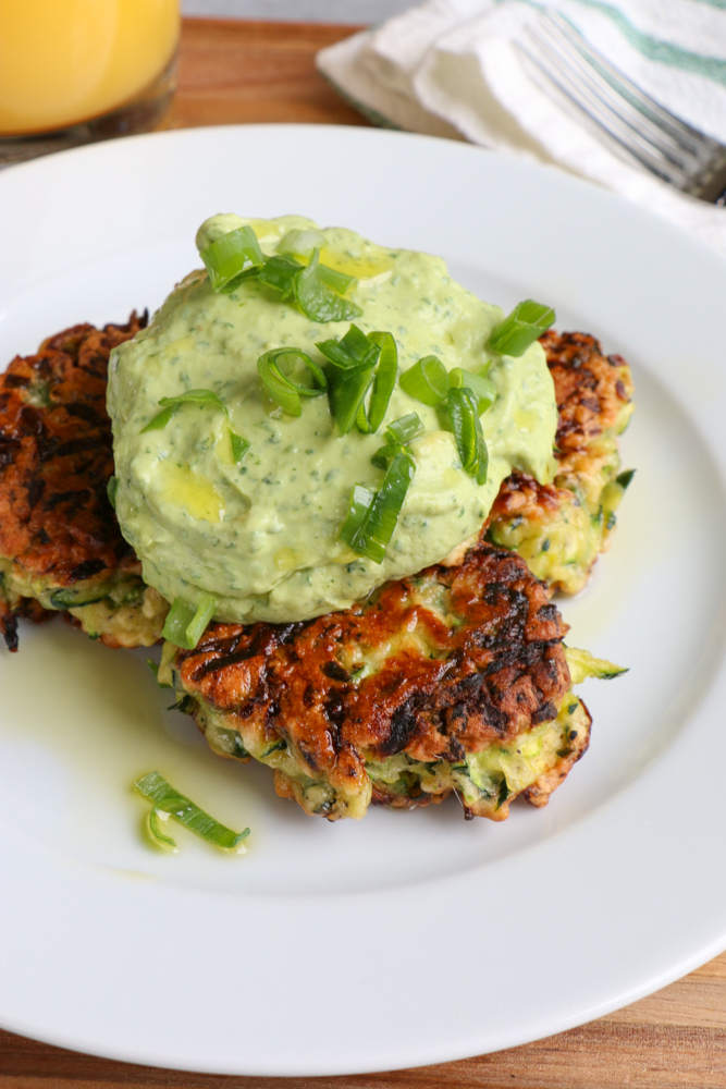Zucchini Fritters with Avocado Crema!! Brunch with a healthy twist! Savory and delicious and topped with a fresh avocado crema!